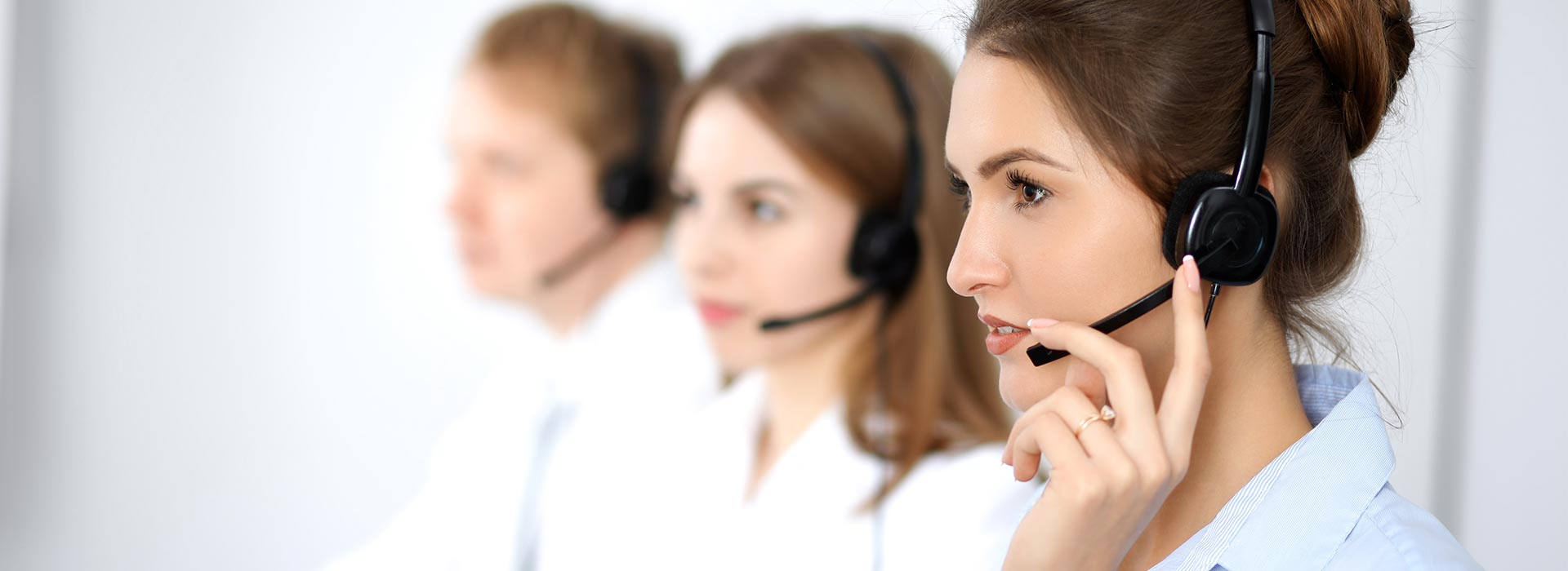 Three people in a call centre situation wearing headsets